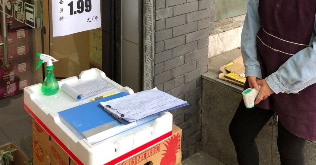A worker outside a fruit shop in Beijing registers customers information, including ID number, phone number and temperature (picture taken 2020:04:28).