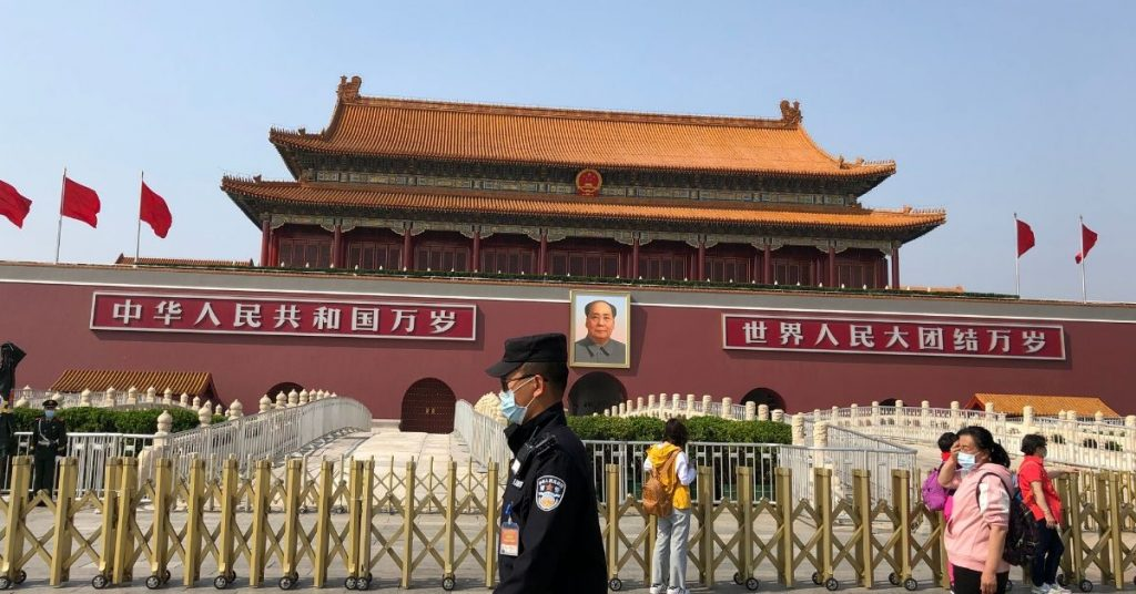 The entrance to the Forbidden City; a security guard walks by as visitors pose for photographs in front of the portrait of Chairman Mao Zedong (picture taken 2020:04:28).